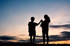 Silhouettez la mère et le garçon jouant avec le petit chien Photographie stock