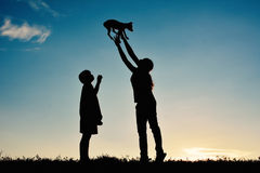 Silhouettez la mère et le garçon jouant avec le petit chien Photos stock
