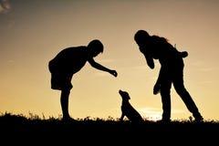 Silhouettez la mère et le garçon jouant avec le petit chien Photo libre de droits