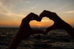 Silhouettez la main dans la forme de coeur avec le lever de soleil au milieu et à l'arrière-plan de plage Photo stock