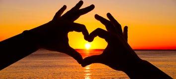 Silhouettez la main dans la forme de coeur et le lever de soleil au-dessus de l'océan Image libre de droits