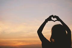 Silhouettez la main des femmes dans la forme de coeur au Ba de coucher du soleil de ciel Photos stock
