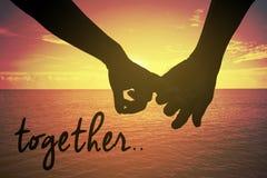 Silhouettez la main haute étroite du crochet de couples le ` s auriculaire ensemble près du bord de la mer à la plage Photos stock