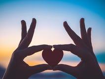 Silhouettez la main tenant le beau coeur pendant le fond de coucher du soleil Photos stock