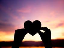 Silhouettez la main tenant le beau coeur pendant le fond de coucher du soleil Photographie stock libre de droits