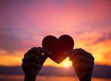 Silhouettez la main tenant le beau coeur pendant le fond de coucher du soleil Photo libre de droits