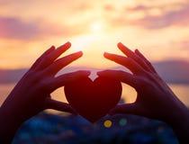 Silhouettez la main tenant le beau coeur pendant le fond de coucher du soleil Images libres de droits