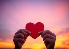 Silhouettez la main tenant le beau coeur pendant le fond de coucher du soleil Photos libres de droits