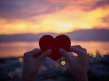 Silhouettez la main tenant le beau coeur pendant le fond de coucher du soleil Photographie stock