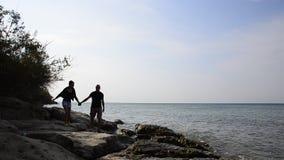 Silhouettez la marche des couples romantiques marchant sur des roches de plage d'océan banque de vidéos