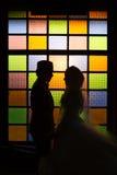 Silhouettez la scène romantique des couples d'amour sur le mur coloré Images stock
