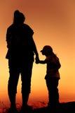 Silhouettez la vue arrière de la mère et de la fille étreignant le togeth de main Photo stock
