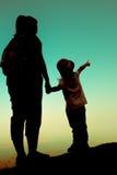 Silhouettez la vue arrière de la mère et de la fille étreignant le togeth de main Photo libre de droits