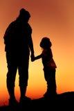 Silhouettez la vue arrière de la mère et de la fille étreignant le togeth de main Image stock