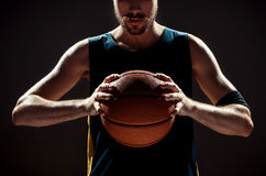 Silhouettez la vue d'un joueur de basket tenant la boule de panier sur le fond noir Image stock