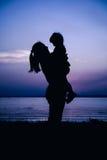 Silhouettez la vue de côté de la mère et de l'enfant appréciant à la rive Image stock