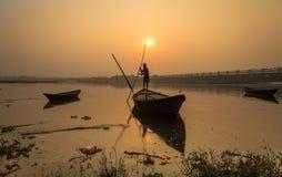 Silhouettez le bateau avec le rameur au coucher du soleil sur la rivière Damodar Photo libre de droits