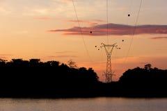 Silhouettez le courrier à haute tension, tour de transport d'énergie au barrage de Sirindhorn dans le temps de matin Photographie stock