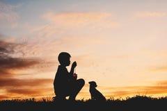 Silhouettez le garçon jouant avec le petit chien sur le coucher du soleil de ciel Image stock