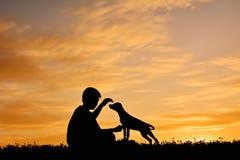 Silhouettez le garçon jouant avec le petit chien sur le coucher du soleil de ciel Photographie stock libre de droits