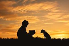 Silhouettez le garçon lisant un livre avec le petit chien Photographie stock libre de droits