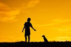 Silhouettez le garçon tenant un papier de fusée et jouant avec le petit chien Images stock