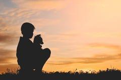 Silhouettez le garçon tenant un papier de fusée et jouant avec le petit chien Photo libre de droits