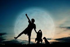 Silhouettez le garçon tenant un papier de fusée et jouant avec le petit chien Photos stock