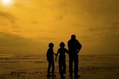 Silhouettez le groupe d'enfants jouant à la plage Image stock