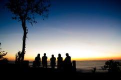 Silhouettez le groupe de personnes se tenant à la falaise et beaucoup de m Image stock