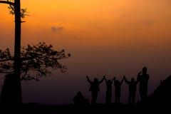 Silhouettez le groupe de personnes se tenant et montrez leur main dans le sunse Photographie stock libre de droits