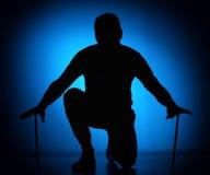 Silhouettez le jeune batteur expressif avec le bâton de tambour sur un fond bleu Images libres de droits