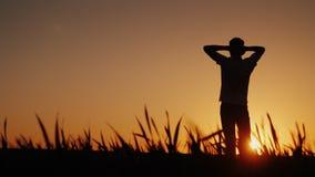 Silhouettez le jeune homme d'A apprécie l'air frais et admire le coucher du soleil Il tient ses mains derrière le dos de sa tête Images stock