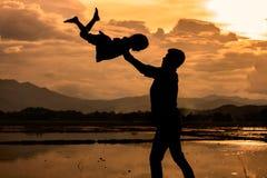 Silhouettez le père jetant son enfant dans le ciel Photo libre de droits