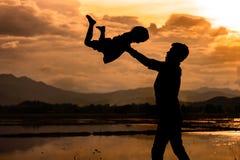 Silhouettez le père jetant son enfant dans le ciel Photographie stock