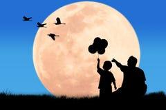 Silhouettez le point de main de père son fils regardant l'oiseau de héron Photographie stock libre de droits
