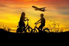 Silhouettez le regard de vélo d'équitation de petit garçon et de petite fille au vol d'avion sur le coucher du soleil Photographie stock