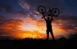 Silhouettez le support d'homme dans la bicyclette de levage d'action photographie stock