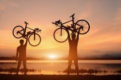 Silhouettez le support pour deux hommes dans la bicyclette de levage d'action au-dessus de sa tête sur le coucher du soleil images stock
