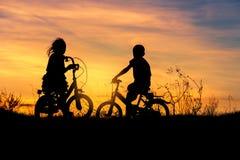 Silhouettez le vélo d'équitation de petit garçon et de petite fille sur le coucher du soleil Photos libres de droits