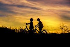 Silhouettez le vélo d'équitation de petit garçon et de petite fille sur le coucher du soleil Photo libre de droits