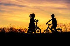 Silhouettez le vélo d'équitation de petit garçon et de petite fille sur le coucher du soleil Photos stock