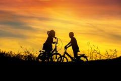Silhouettez le vélo d'équitation de petit garçon et de petite fille sur le coucher du soleil Photographie stock