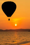 Silhouettez les ballons à air chauds flottant au-dessus de la plage tropicale sur le coucher du soleil Photos stock