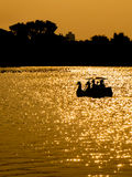 Silhouettez les couples dans le bateau de pédale de cygne sur le coucher du soleil Image stock