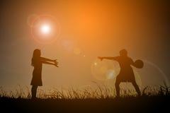 Silhouettez les enfants jouant le football sur le coucher du soleil de ciel Temps dessus Photos libres de droits