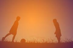 Silhouettez les enfants jouant le football sur le coucher du soleil de ciel Temps dessus Images libres de droits