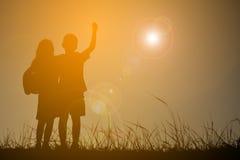 Silhouettez les enfants jouant le football sur le coucher du soleil de ciel Temps dessus Photo stock