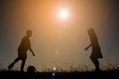 Silhouettez les enfants jouant le football sur le coucher du soleil de ciel Temps dessus Images stock