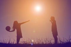 Silhouettez les enfants jouant le football sur le coucher du soleil de ciel Temps dessus Photographie stock
